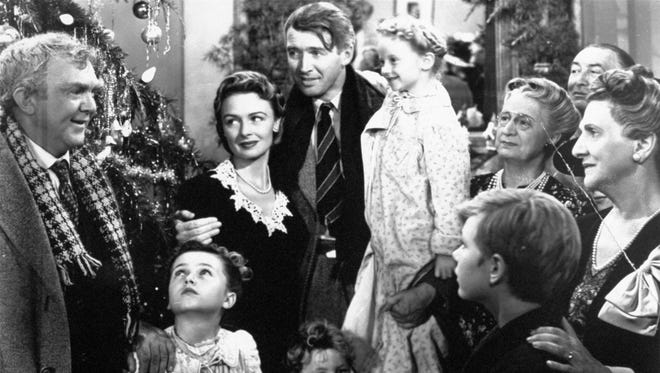 "James Stewart as George Bailey, center, is reunited with his wife, played by Donna Reed, and family during the last scene of Frank Capra's ""It's a Wonderful Life."""