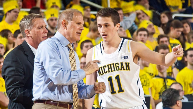 Michigan head coach John Beilein gives instructions to Michigan guard Andrew Dakich (11) at Crisler Center, Jan. 27, 2015. Michigan won 58-44.