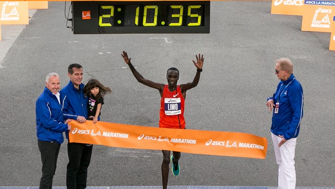 Daniel Limo, center, from Kenya, crosses the finish line to win the Los Angeles Marathon in Santa Monica, Calif.,  March 15.