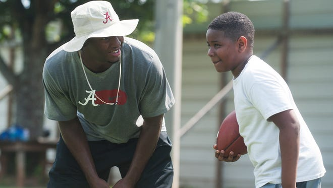 Nick Perry works with young players as they run drills at the S3 Football Camp at the Prattville High School campus in Prattville, Ala. on Saturday July 11, 2015.