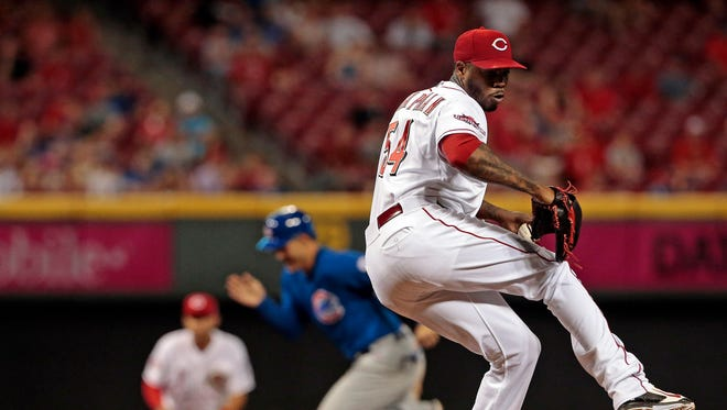 Cubs second baseman Addison Russell steals third base as Reds closer Aroldis Chapman delivers a pitch during a 2015 game.