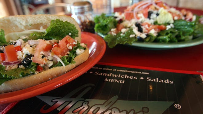 Two items from Ardovino's Pizza, 1879 N. Zaragoza: a vegetarian sandwich with spinach, mushrooms, sliced black olives, green and red peppers, red onion, lettuce, sliced tomato, and feta and mozzarella cheese, drizzled with the house Italian dressing; and a garden green salad with mixed baby greens topped with feta cheese, red onion, sliced black olives, artichoke hearts and diced fresh tomato, all tossed in Italian dressing.