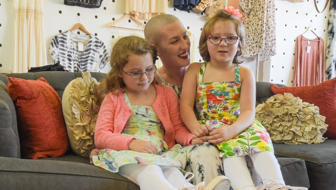 Zoe and Lucy Sonnier with their mom, Leah Maxwell, at her store,  Three Little Birds.