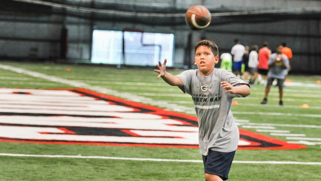 Isaac Perez catches a pass at the Cajuns' youth football camp last weekend.