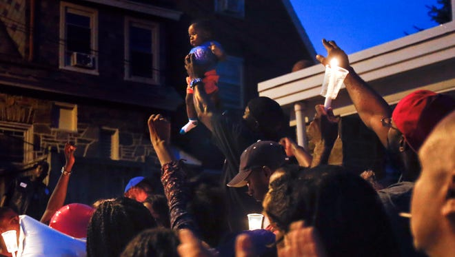 """Kurtis Davis holds up Jordan, the 6-month-old son of shooting victim Keshall """"KeKe"""" Anderson, to the crowd during a memorial three days after she was killed by a bullet meant for someone else on the 200 block of W. 20th Street in Wilmington."""