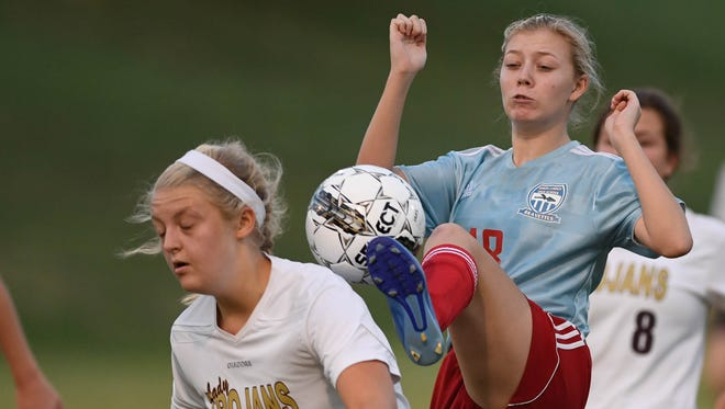 Union County's Chloe Dunford (right) and Webster County's Maddy Mitchell battle for control of the ball as Webster teammate Olivia Utley looks on as Union County plays Webster County in the Girls District Soccer Tournament in Morganfield Monday, October 10, 2016.