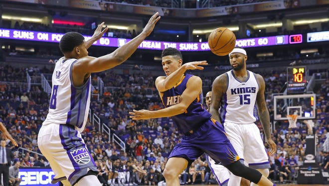 Phoenix Suns guard Devin Booker  makes a no-look pass against the Sacramento Kings during the first half off their NBA game Wednesday, Oct. 26, 2016 in Phoenix, Ariz.