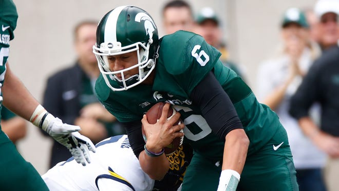 Michigan State Spartans quarterback Damion Terry battles for extra yards against the Michigan Wolverines at Spartan Stadium on Oct. 29, 2016.