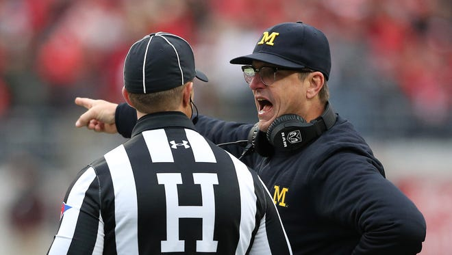 Michigan Wolverines head coach Jim Harbaugh discusses a call with an official.