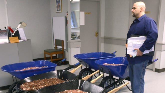 Nick Stafford waits for his number to be called Wednesday, Jan. 11, 2017, as he stands beside of 5 wheelbarrows full of change, mostly pennies, at the DMV in Lebanon, Va. Stafford was paying the sales tax on two cars that he was titling. Stafford had paid $165 to file three lawsuits in Russell County General District Court: two against specific employees at the Lebanon DMV and one against the DMV itself., which means he spent $1,005 to get 10 phone numbers and the satisfaction of delivering 300,000 pennies. Not to mention the nearly $3,000 he paid the DMV for the cars.
