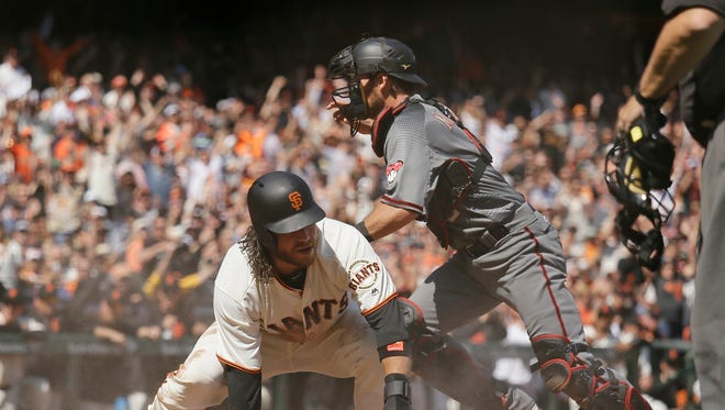 San Francisco Giants' Brandon Crawford, left, scores as Arizona Diamondbacks catcher Jeff Mathis, right, chases after the ball in the fourth inning of a baseball game, Monday, April 10, 2017, in San Francisco.