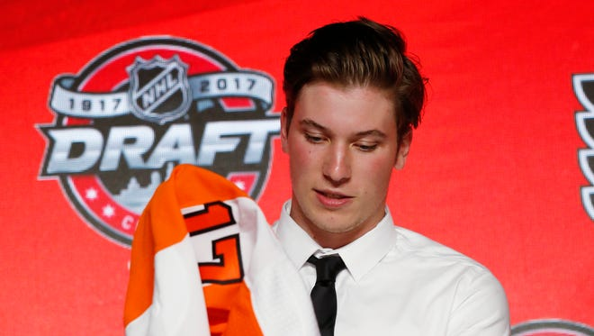 Nolan Patrick puts on a Philadelphia Flyers jersey after being selected by the team in the first round Friday.