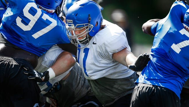 University of Memphis offensive lineman Gabe Kuhn (middle) makes a block during field goal drills during practice Monday afternoon.