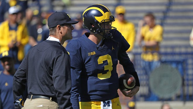 Michigan head coach Jim Harbaugh and quarterback Wilton Speight chat prior to the start of the game against Cincinnati at Michigan Stadium on Sept. 9, 2017.