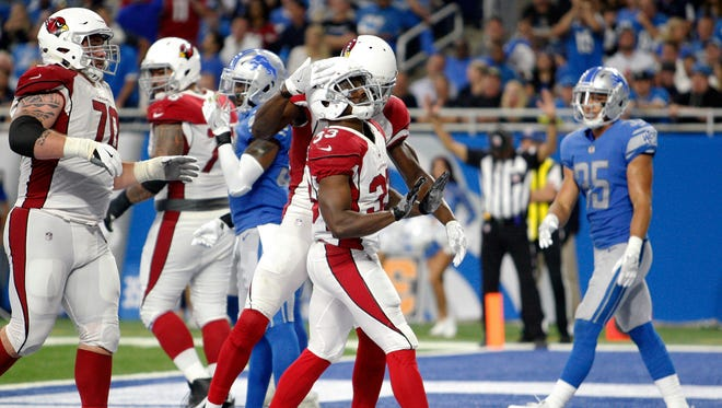 Arizona Cardinals running back Kerwynn Williams (33) celebrates with teammates after rushing for a touchdown during the third quarter against the Detroit Lions at Ford Field.