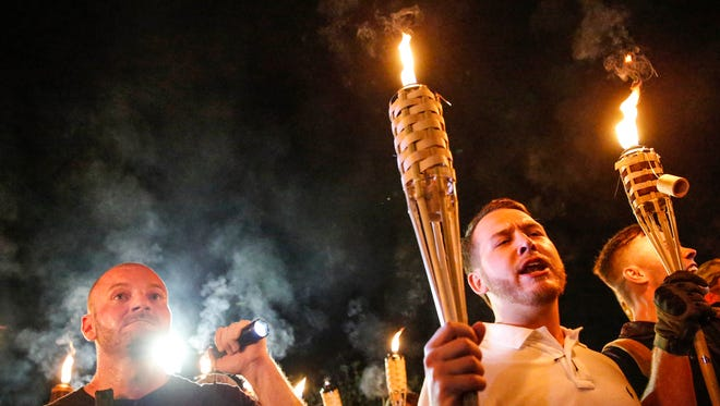 White nationalist Christopher Cantwell, left, shines a flashlight into the faces of counter protesters and media cameras Aug. 11, 2017, on the University of Virginia campus in Charlottesville, Va.