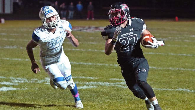 Muskego's Austin Kaltenbrun eludes Oak Creek's Zach Peterson as he heads into the endzone for Muskego's second tochdown of the the night at Muskego on Oct. 20.
