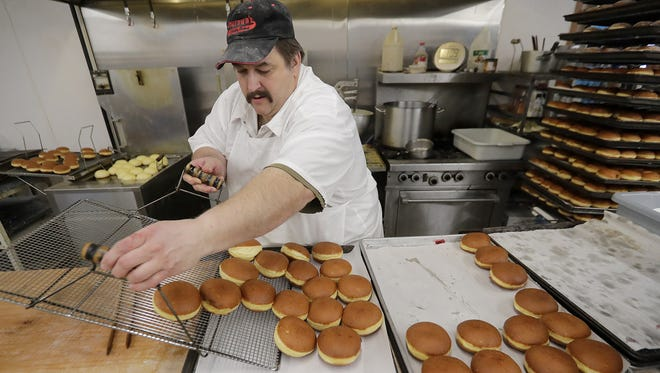 Greg Smurawa unloads a tray of freshly fried Paczki at Smurawa's Country Bakery Monday, February 12, 2018 in Pulaski, Wis. The bakery is renowned for their pastries eaten as a Fat Tuesday tradition which Smurawa and his extended family are busy making by the thousands as the Lenten season gets under way.
