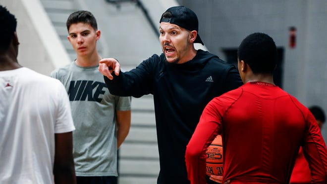 Memphis assistant Mike Miller, shown here in March before his hiring, instructs his son, Mason (left), and T.J. Madlock (red).