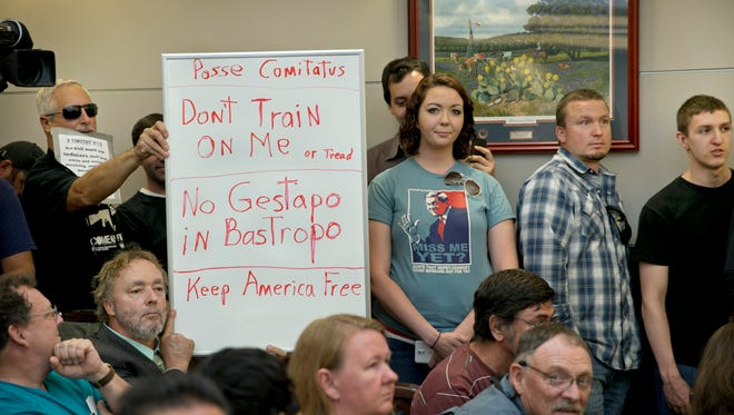 Bob Welch, standing at left, and Jim Dillon, hold a sign at a public hearing about the Jade Helm 15 military training exercise in Bastrop, Texas, April 27, 2015.