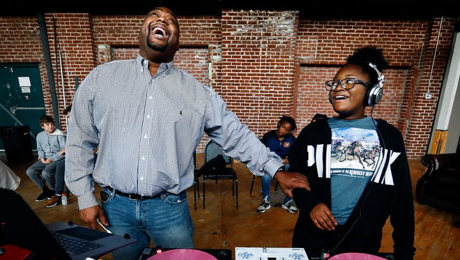 """Bryan """"DJ Quiji"""" Barnett (left) jokes with camper Ja'Kailah Morris, 13, (right) during Camp DJ Memphis at Minglewood Hall Friday afternoon. This week, several professional DJ's came together to host the first annual camp in Memphis. Campers learned how to perform beat matching, song dropping and mixing on high-tech virtual turntables."""