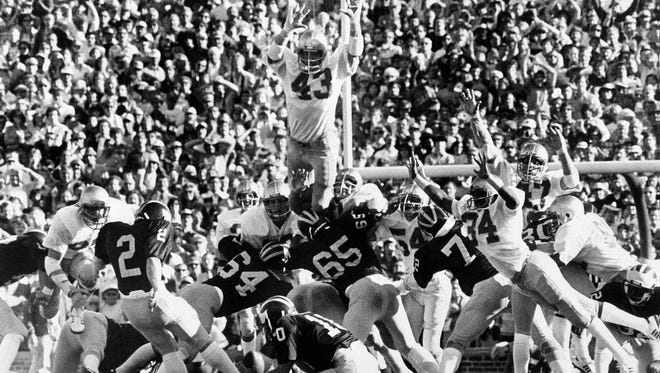 University of Notre Dame's Bob Crable (43) steps to the shoulders of the Notre Dame line to block a field goal attempt by University of Michigan's Bryan Virgil (2) with B.J. Dickey (10) holding at seven seconds remaining in the game in Ann Arbor, Michigan, on Saturday, Sept. 15, 1979. The block gave Notre Dame a 12-10 victory over Michigan.