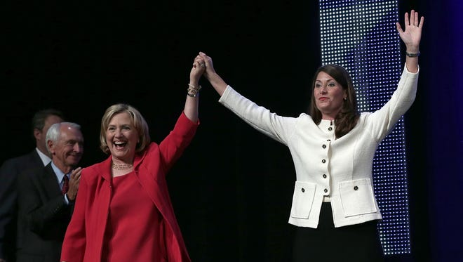 Former U.S. Secretary of State Hillary Clinton (left) campaigns with U.S. Senate candidate and Kentucky Secretary of State Alison Lundergan Grimes on October 15 in Louisville.