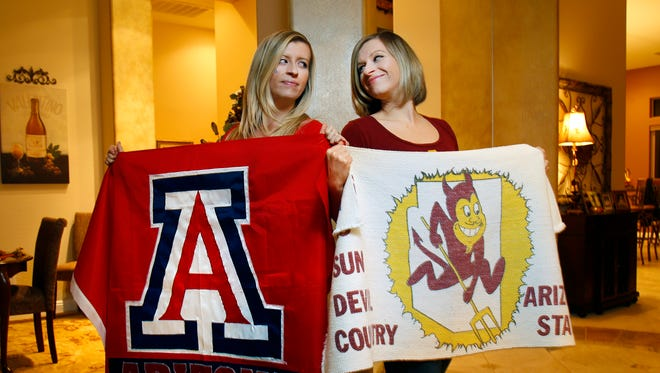 Twins Janelle (left) and Kayla Drumwright have different loyalties. They are both 2006 graduates and avid sports fans for their respective schools' teams.