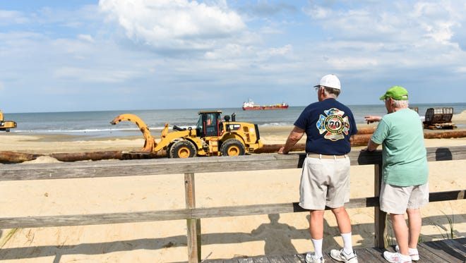 Local shore residents Bob Maxwell (left) and Jim Citron watched construction for the beach replenishment project in Bethany Beach on Thursday.
