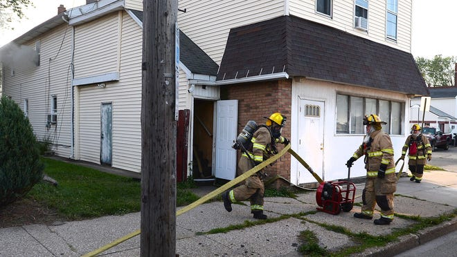 Erie firefighters extinguish a structure fire on the second floor of 1602 Sassafras St. in Erie on Friday. Officials believe the fire was started by a candle.