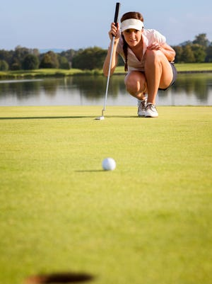 Woman golf player squatting to analyze the green for putting the golf ball into the hole.