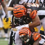 Pittsburgh Steelers running back DeAngelo Williams (34) carries the ball as Cincinnati Bengals outside linebacker Vontaze Burfict (55) and cornerback Dre Kirkpatrick (27) tackle in the first half at Paul Brown Stadium.