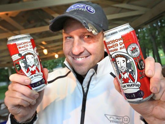 Sean O'Connor, owner of Flat 12 Bierwerks, shows off a couple cans of Hinchtown Hammer Down, a German pilsner-style beer named after IndyCar driver James Hinchcliff. O'Connor had his special brew for attendees of the Vintage Wheels and Wine event at Conner Prairie.