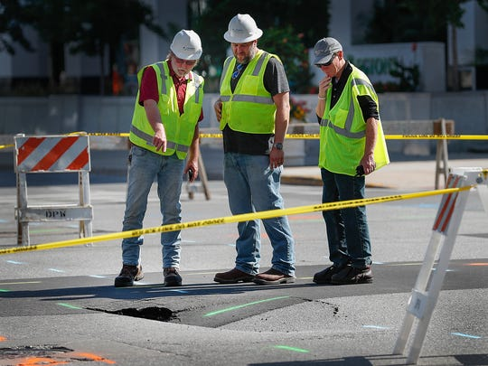 Workers continue to survey the scene of the sinkhole