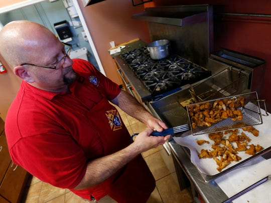 Al Snyder, a trustee with the Knights of Columbus council 644, fries up a basket of catfish nuggets Friday, March 20, 2015, at the church's weekly lenten fish fry at Bascilica of St. John in Des Moines. Organizers said about 160 pounds of fish are fried or baked up each week for the dinner.