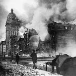 18 Apr 1906 --- Troops walk east along Market Street after the devastating earthquake of 1906. The tall Call building burns in the distance. --- Image by © Corbis