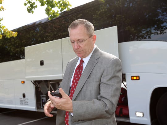 Jeff Long checks scores on his phone.