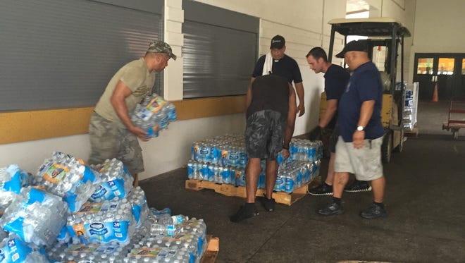 Members of Andersen Air Force Base 36 CES HVAC Shop unload their 78 cases of donated water to help fill a 40-foot container bound for Saipan on Saturday at the University of Guam Calvo Field House.