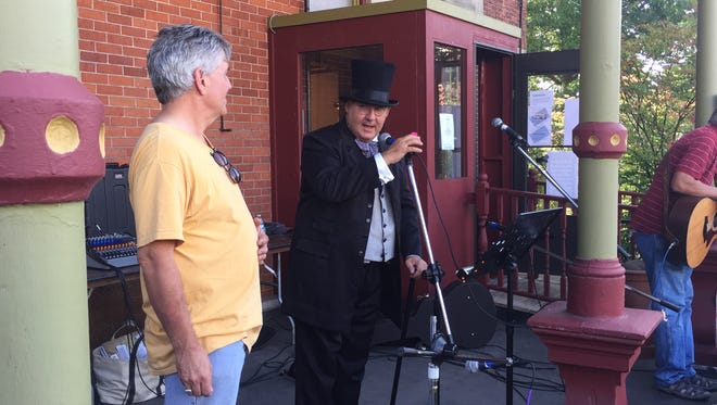 J. Tracy Hermann, City of Poughkeepsie councilmember, dressed at Matthew Vassar, and J. Andrew Burgreen, executive director at the Cunneen-Hackett Arts Center, announce the raffle winners at the Vassar Street Brew Fest.