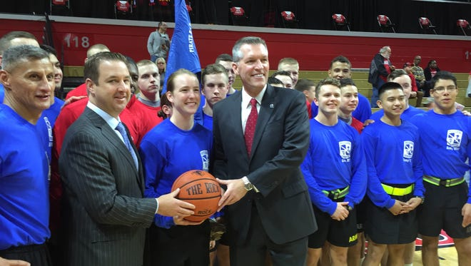 Seton Hall AD Pat Lyons (left) and Rutgers AD Pat Hobbs (right) accept the game ball from ROTC members who ran it 21 miles from Walsh Gym to the RAC prior to the 2015 meeting.