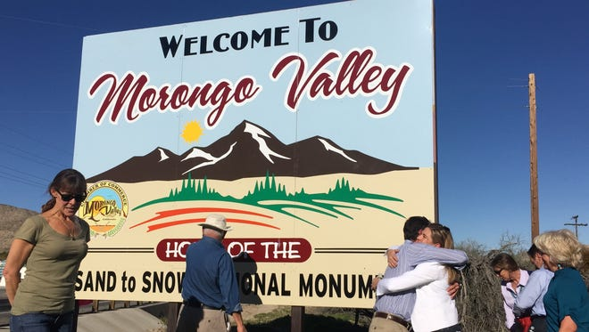 """Frazier Haney and April Sall embrace after the unveiling of a new sign in Morongo Valley in February 2016, christening the High Desert town as """"Home of the Sand to Snow National Monument."""""""