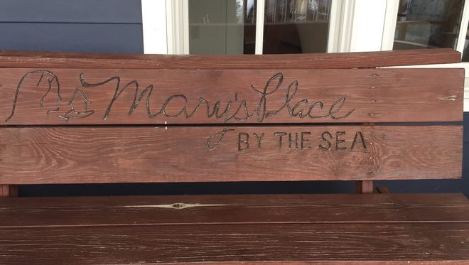 A bench with inscription and logo of Mary's Place by the Sea.