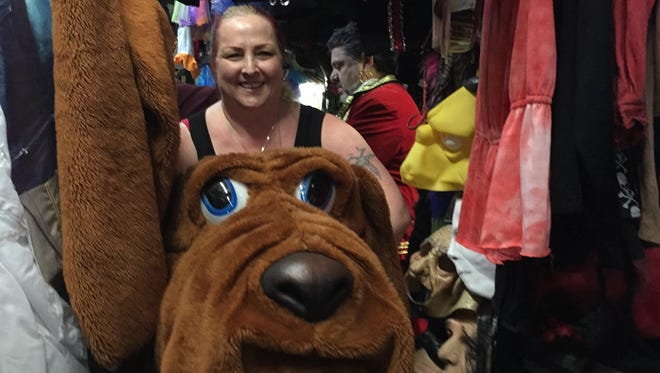 Lisa Penzimer, makeup artist at Arlene's Costume Shop in Toms River, carries an outfit for McGruff the Crime Dog as a patron behind her gets fitted as Captain Morgan.