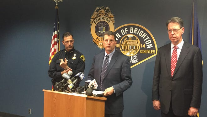 Brighton Police Chief Mark Henderson, center, speaks at a press conference Tuesday where findings from a racist flier investigation were revealed.