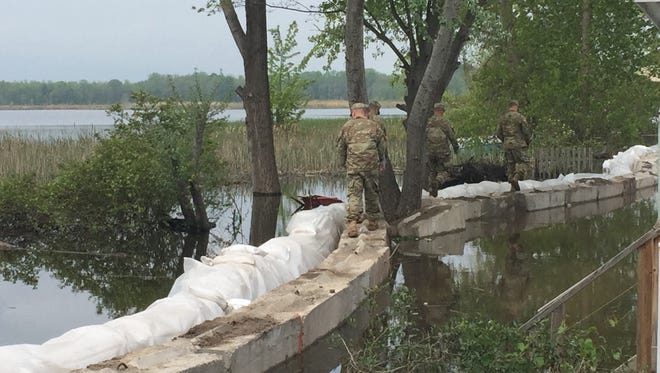National Guard troops inspect their work on a retaining wall along Round Pond in Greece on Saturday, May 27.