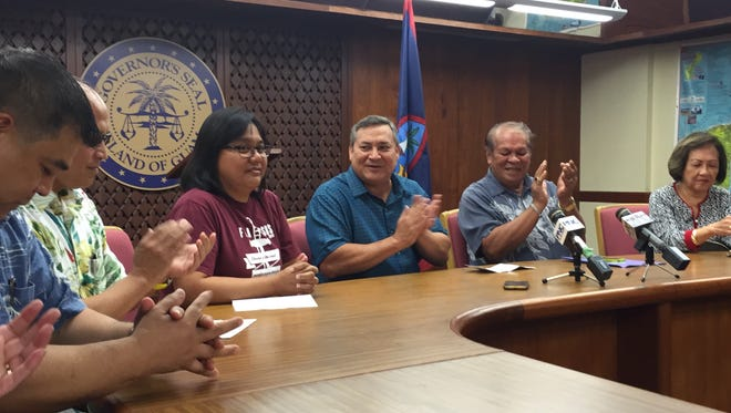 Guam Education Board Chairman Peter Alecxis Ada, second from right, applauds after Gov. Eddie Calvo, in dark blue shirt, hands over a nearly $1.5 million check on June 16, 2017, for summer repairs at Simon Sanchez High School and other schools.