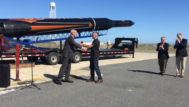 Bill Wrobel, executive director of NASA Wallops Flight Facility, greets John Garvey, chief technology officer of Vector Space Systems, during a demonstration of the Vector-R launch vehicle on Wallops Island on Thursday, Oct. 19.