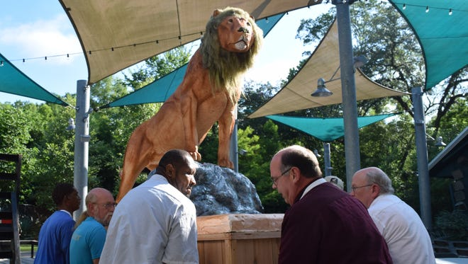 Mark Atwood (right), owner of Atwood's Bakery, and Atwood's Bakery employee Dameion Tillman (left) help move a cake made in the shape of a lion onto the pavilion at the Alexandria Zoo Saturday. Jennifer Atwood came up with the idea to create the cake in the shape of a lion for the zoo's 90th anniversary celebration.