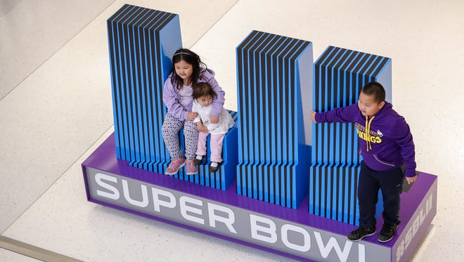 Children pose on a Super Bowl logo at the Mall of America. Do they know that it is the Roman numeral for 52?