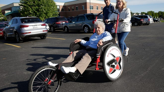Liz and Jack Wilson, daughter-in-law and son of 86-year-old Lorraine Wilson, seated, get accustomed Wednesday to the borrowed racing wheelchair they'll be using to push her in Saturday's Bellin Run.